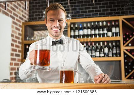 Handsome bar tender holding a pint in a pub