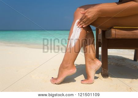 Woman Applying Sunblock Cream On Leg On Beautiful Tropical Beach With White Sand On Summer Vacation.