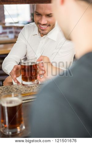 Handsome bar tender giving a pint to customer in a pub