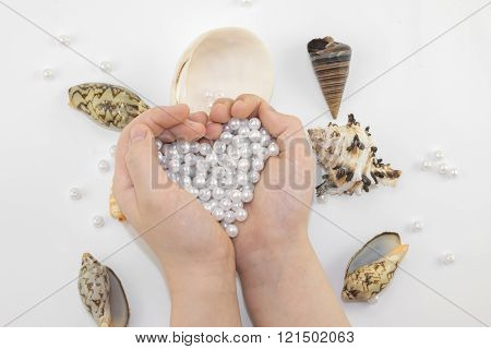 hands with pearl beads and seashells