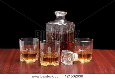Decanter And Three Glasses With Whiskey On A Wooden Table