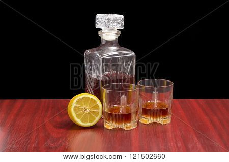 Decanter And Two Glasses With Whiskey And Lemon