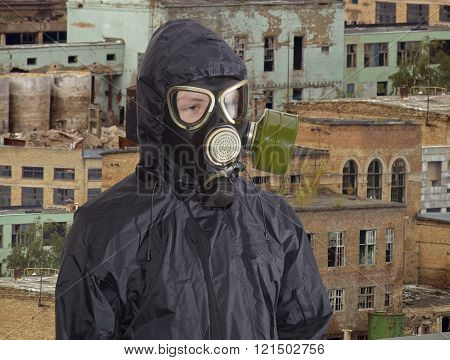 Person in gas mask against the backdrop of abandoned production