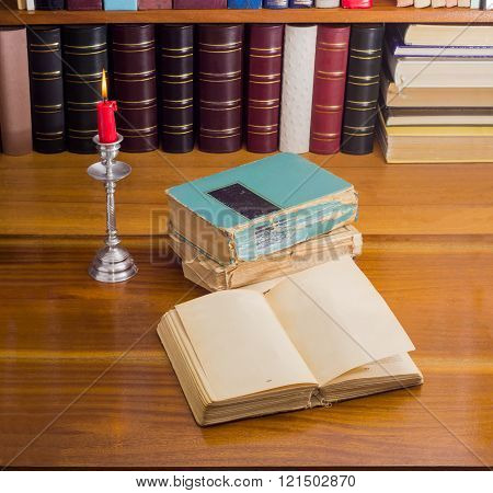 Open Old Book And Stack Of Several Books By Candlelight