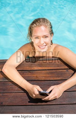 Portrait of beautiful woman leaning on poolside and typing a text message
