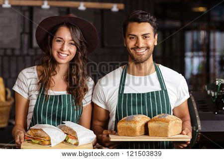 Smiling baristas holding bread and sandwiches in the bar