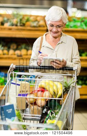 Smiling senior woman checking list in supermarket