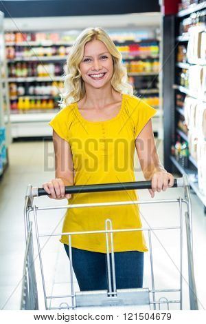 Smiling woman pushing cart and looking at the camera
