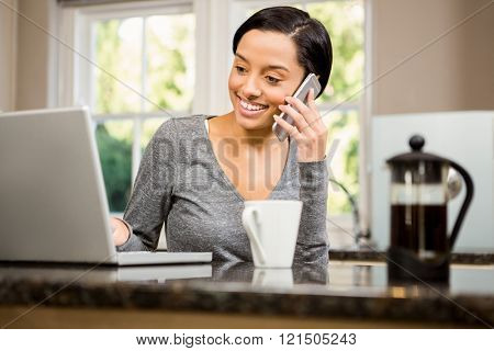 Smiling brunette on phone call while looking at laptop in the kitchen