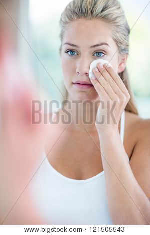 Woman wiping her face with cotton pad in the bathroom