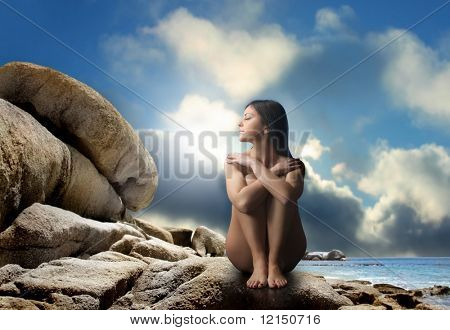 naked woman on stones at sea