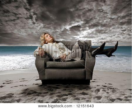 senior woman sitting on an armchair on the beach