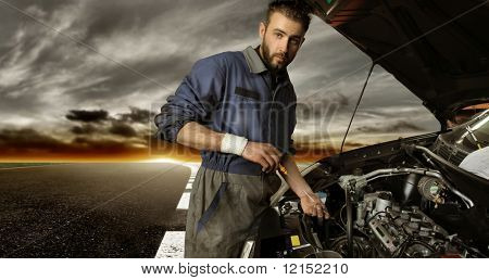 Auto mechanic checking car on the street