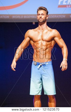 Male Fitness Model Shows His Physique In Swimsuit Om Stage