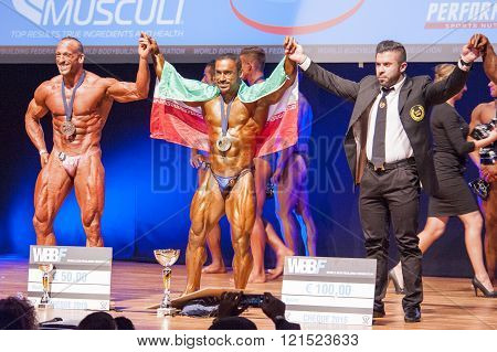 Male Bodybuilders Celebrate Their Championship Victory On Stage With Officials