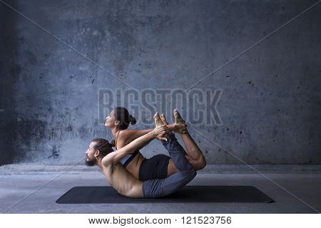 Acroyoga practice, man and woman practice bow pose on a urban background