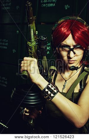 Military redhead girl with automatic rifle posing in a storage