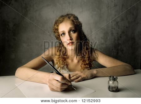 Beautiful girl writing a letter with ink pen