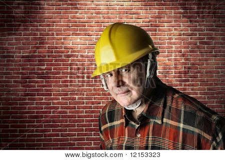 portrait of worker with an hardhat against a bricks wall