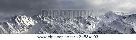 Panoramic View On High Sunlight Mountains And Storm Sky Before Blizzard