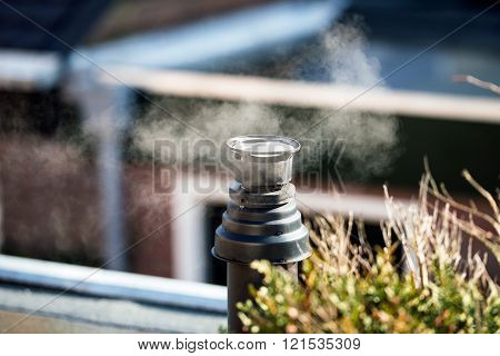 Steam from chimney on roof.