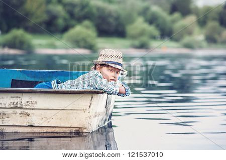 Little Boy Lying In The Old Boat On A Pond At The Summer Evening