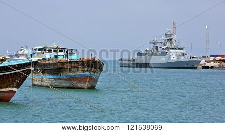 GULF OF ADEN, PORT OF DJIBOUTI â?? FEBRUARY 08, 2016: Traditional old style wooden fishing and cargo ships and EU WARSHIP F-262, German multipurpose corvette on background