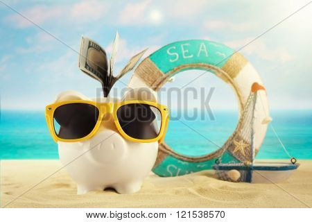 Piggy bank with dollar banknotes, sunglasses on a sand. Holiday money concept