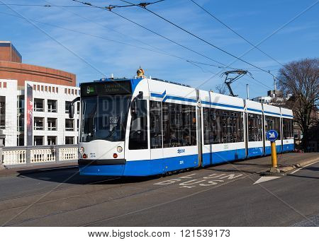 AMSTERDAM NETHERLANDS - 16TH FEBRUARY 2016: A typical blue and white Tram on a road in Amsterdam during the day. People can be seen on the tram.