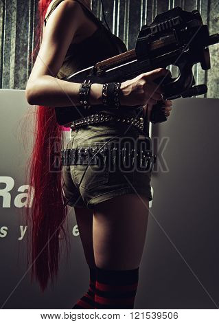 Redhead young lady posing with weapons. Rear view.
