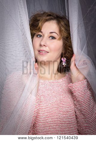 Portrait closeup of hiding in tulle curtain beautiful woman in pink sweatr happy smiling and looking at camera