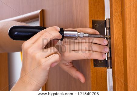 hands with screwdriver screwing hinge on a door closeup