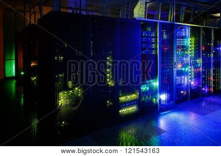server room in the dark, with bright colored lights