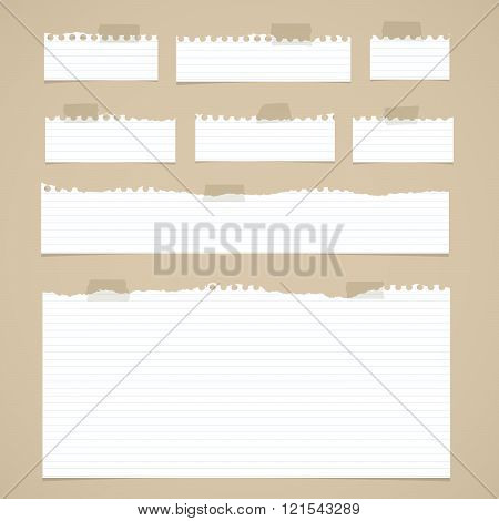 Pieces of torn white lined notebook paper with sticky tape on brown background