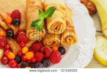 Breakfast. Pancakes with honey and fresh berries - raspberries, cranberries, sea buckthorn