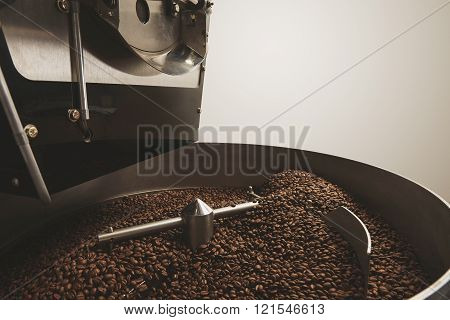 Hot freshly baked aromatic and dark coffee beans in the best professional roasting machine twisting