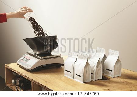 Woman hand pours freshly baked aromatic coffee beans to weight before packing in bulk bag package. P