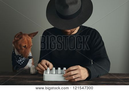 Musician Twist Knobs On Mixer Near His Curious Dog