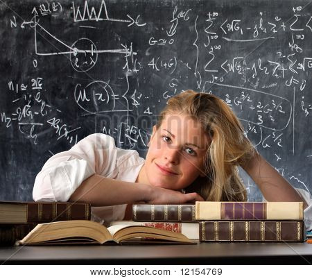 happy female student with books and blackboard