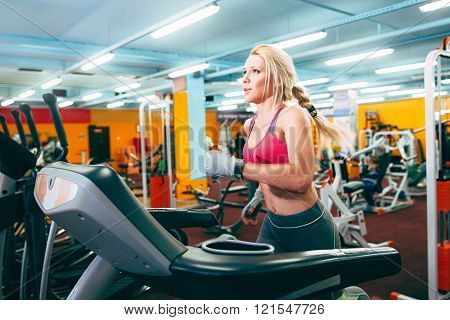 Athletic girl runs on treadmil in gym