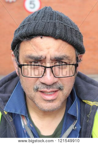 PORTSMOUTH, ENGLAND, 10TH MARCH 2016: A portrait of an ethnic manual worker wearing a hat while working outside in portsmouth, england, 10th march 2016
