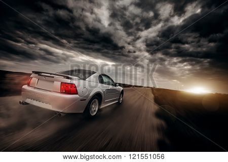 Saratov, Russia - April 13, 2013: Grey car Ford Mustang fast drive on dirt road at dramatic clouds sunset
