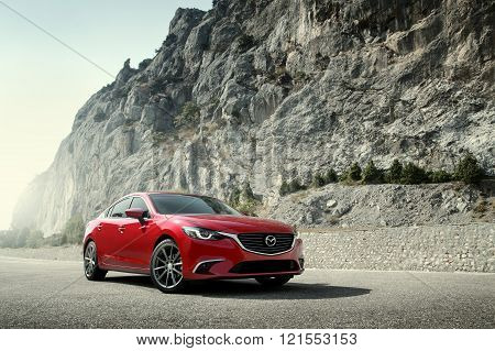 Crimea Russia - September 20 2015: Red car Mazda standing on the road near mountains at daytime