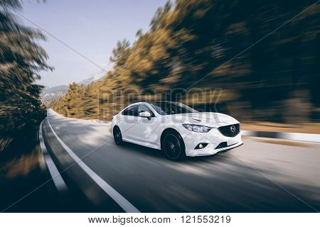 Crimea, Russia - September 20, 2015: White Car Mazda Speed Driving On Asphalt Road At Daytime