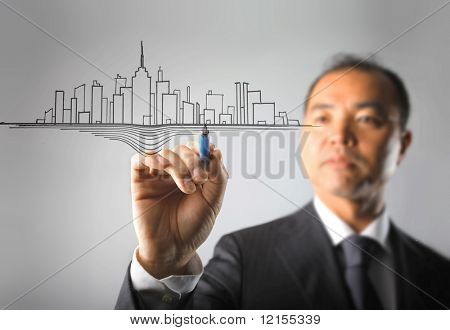 asian businessman drawing a modern city