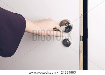 Woman Hand Opens A Door To A Dark And Unknown Room.