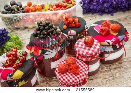 processed strawberries and black currants to jam and bottled in glasses