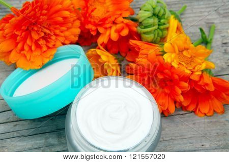 marigold cream in glass with flowers on wood