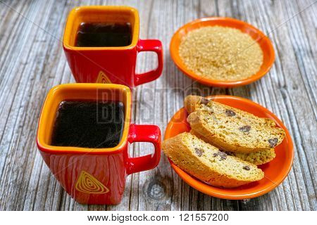 Dessert two cups with espresso coffee raw brown sugar and amandel cantuccini on rustic wooden backgound