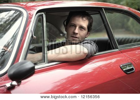 portrait of man seated in a vintage car